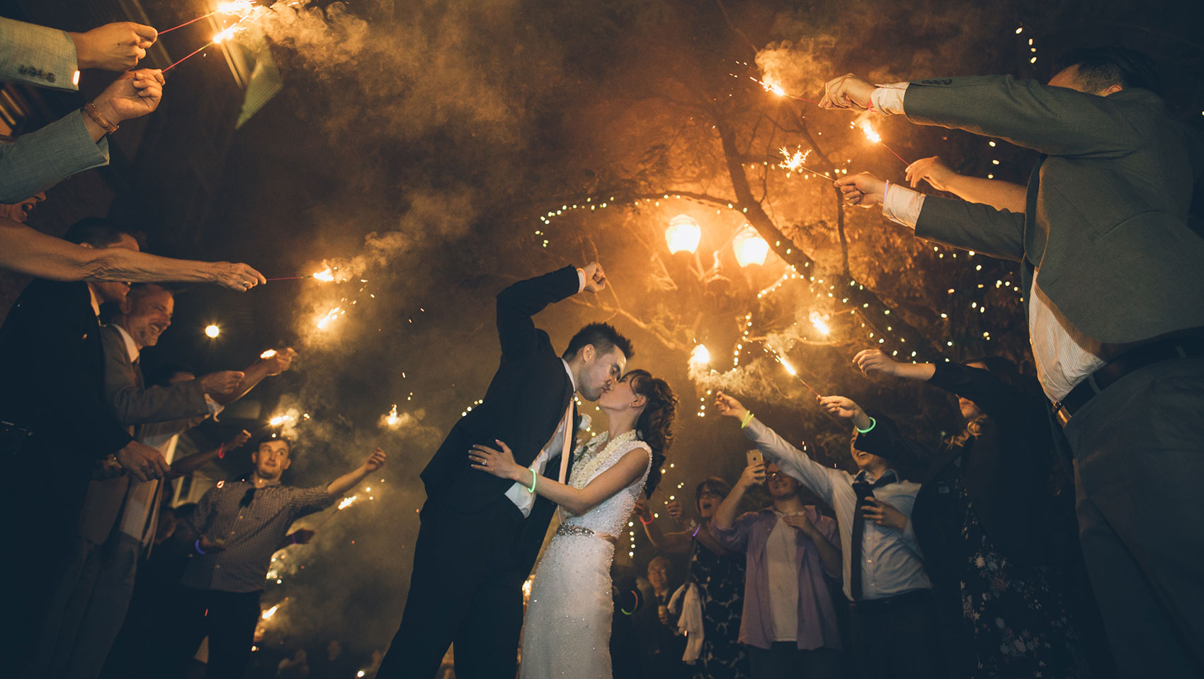 newlywed couple kissing while guests hold lit sparklers over their heads outside at night