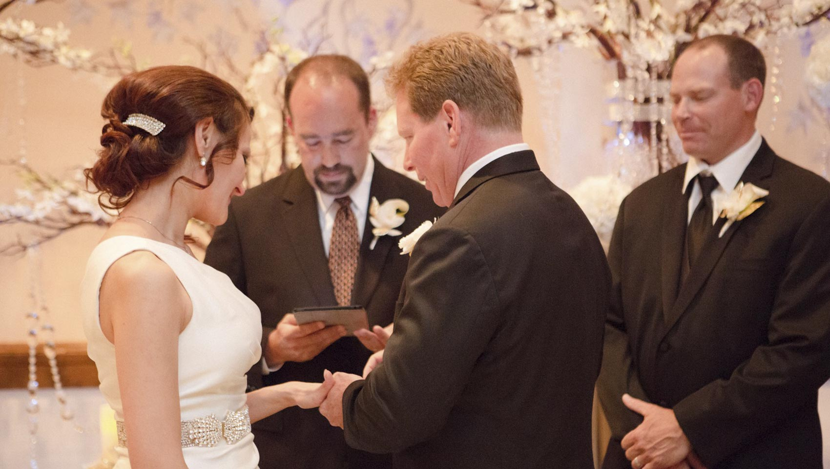 groom placing ring on bride at wedding ceremony