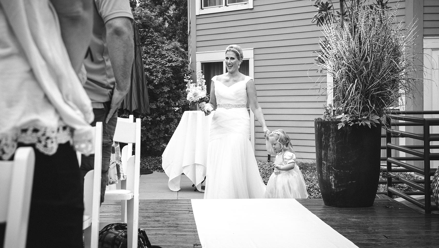 bride with child walking down aisle at outdoor hotel wedding venue
