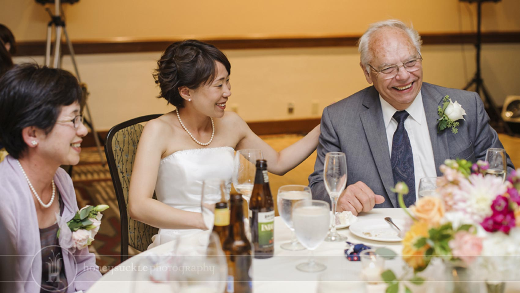 bride sitting and smiling with parents at wedding reception